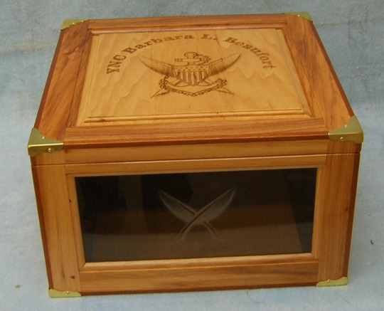 hickory/pecan hat box with yeoman symbol and crossed quills laser engraved on the top with the rank and name. The yeoman feathers are engraved on the front glass panel.