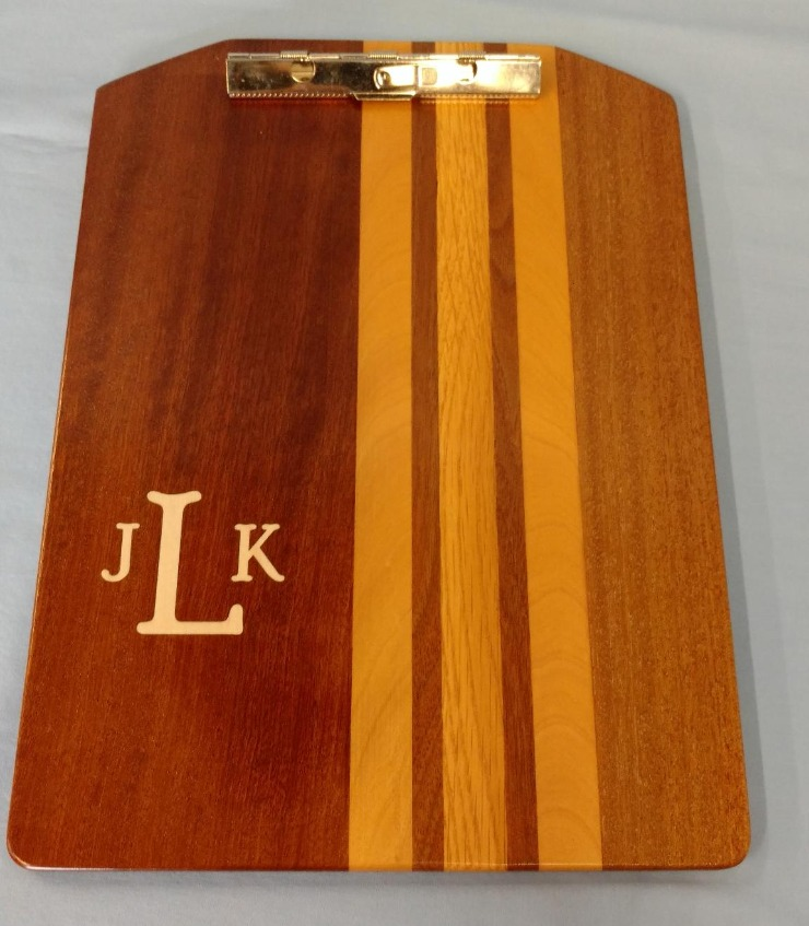 The laminated clip boards are fabricated from various hardwoods. The boards are 9.5 inches wide x 13 inches long with a low profile clip. Several of the boards have  had monogram inlays .
