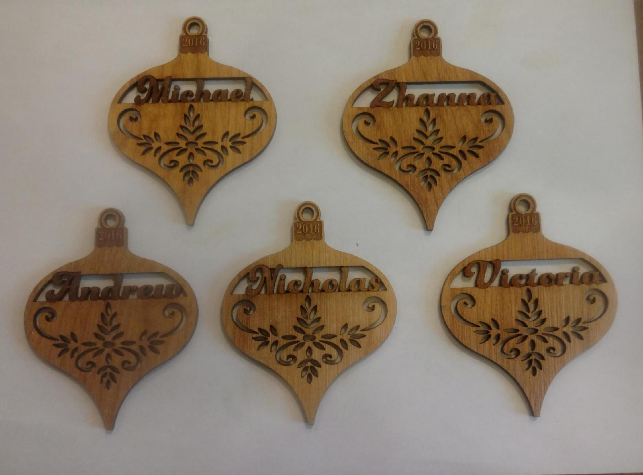 The Christmas ornaments are laser engraved and cut out around the names. There are a couple different designs.