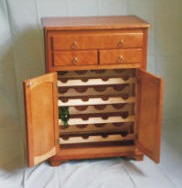 The wine cabinet is solid cherry with maple wine rack. The finish is hand rubbed furniture wax. The cabinet was built when I opened the workshop.