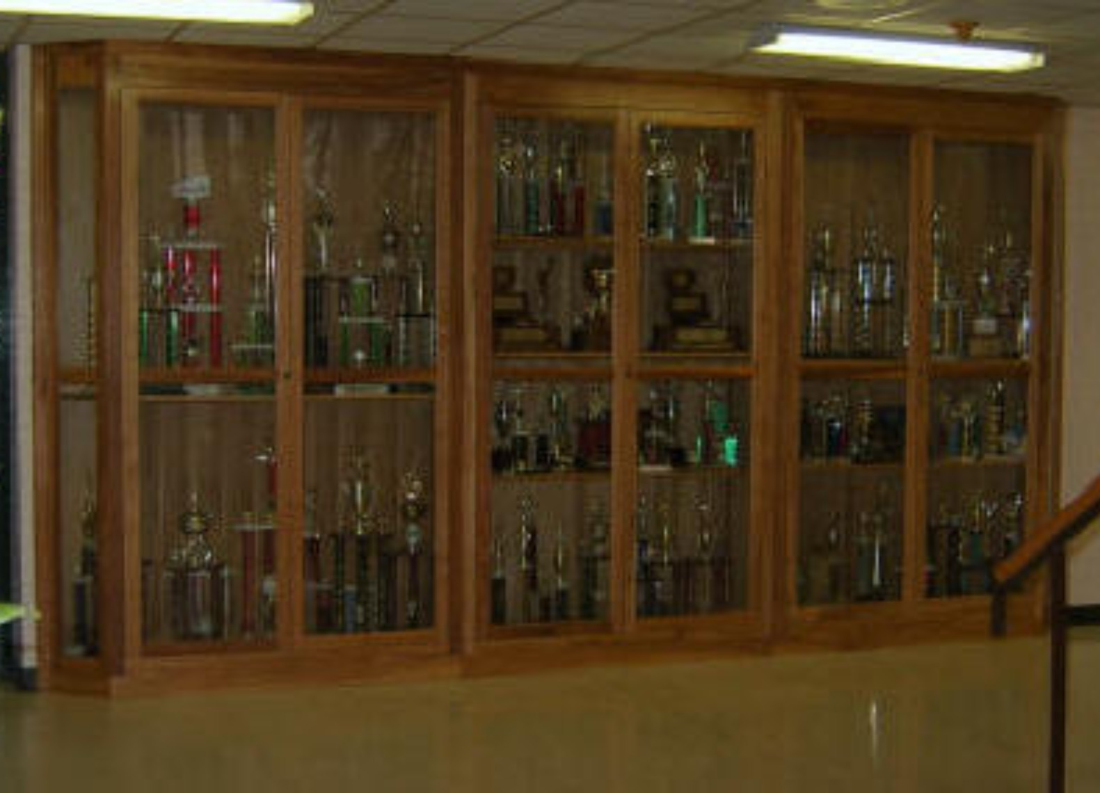 This set of trophy cases was built for a local high school. The cases are 21 feet across and 9 feet high and were built in three sections. Each section sits on a 4 inch base which allowed the units to be raised upright and fit close to the ceiling.