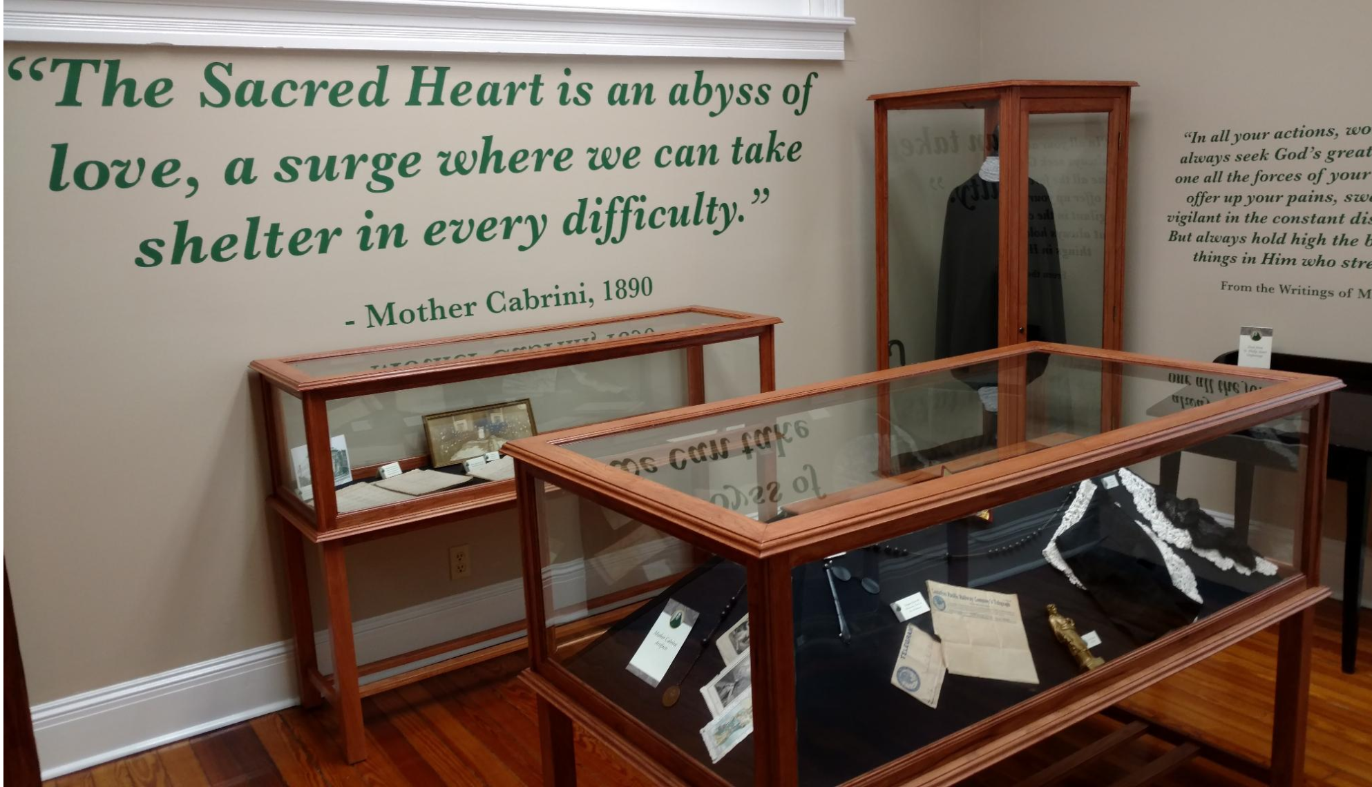 The display cases were built for the Mother Cabrini exhibit at a local high school. The two photos show the five cases that were built. The two in the corner display her habit and the other cases display memorabilia and historical documents.