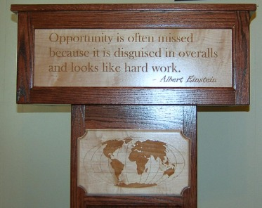 Podium with world map and quotation laser engraved. There is also a dedication plaque inside.